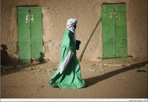 A Malian man dressed in green walks between green doors of closed shops in Gao, Feb. 5, 2013. 